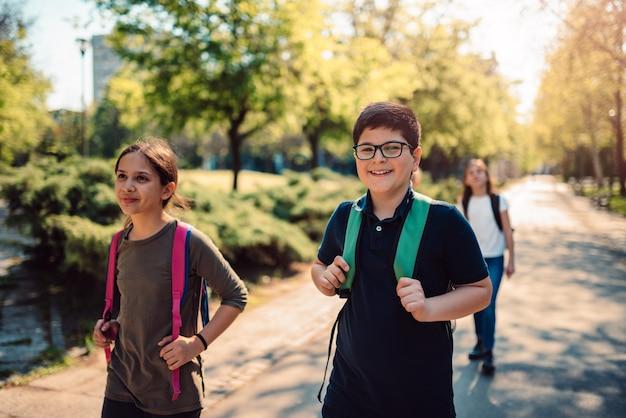 Szczęśliwe dzieci ze szkoły idą razem do szkoły