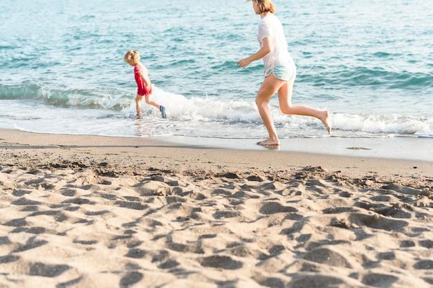 Szczęśliwe dzieciaki na wakacjach nad morzem biegają po wodzie chłopiec i dziewczynka bawią się na plaży latem...