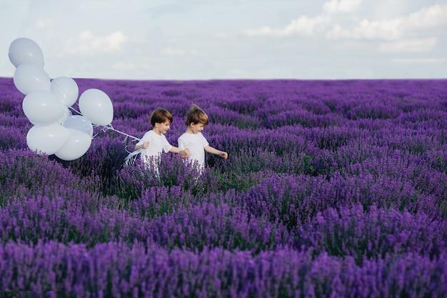 Szczęśliwe dzieciństwo dwoje małych dzieci biegnie przez lawendowe pole