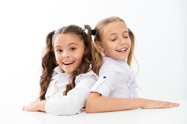 Szczęśliwe dzieciństwo. urocze uczennice. powrót do szkoły. koncepcja edukacji. piękne dziewczyny najlepsi przyjaciele. oficjalny styl. uczennice siedzą przy biurku białe tło. emocjonalni przyjaciele uczennic.