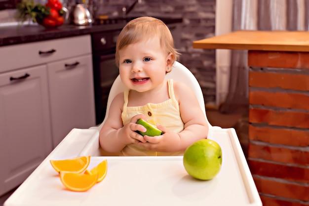 Szczęśliwe dziecko 10-12 miesięcy zjada owoce: pomarańcza, jabłko. portret szczęśliwa dziewczyna w highchair w kuchni