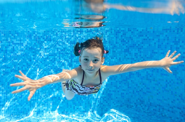 Szczęśliwe dziecko aktywne pływa pod wodą w basenie