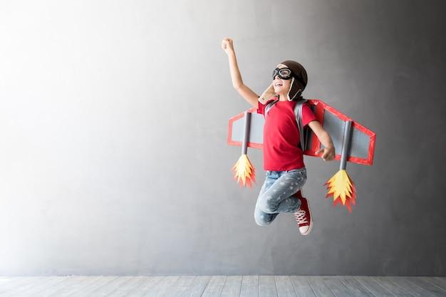 Szczęśliwe dziecko bawi się plecakiem odrzutowym zabawki