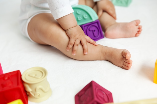 Szczęśliwe dziecko bawi się z kolorowych klocków na podłodze, naturalne światło