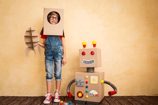 Szczęśliwe dziecko bawi się zabawkami robota w domu. innowacyjna technologia i koncepcja sukcesu