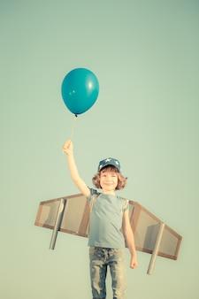 Szczęśliwe dziecko bawi się zabawkami skrzydłami na tle nieba latem. stonowany w stylu retro