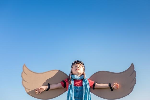 Szczęśliwe dziecko bawi się zabawkowymi skrzydłami na tle błękitnego nieba