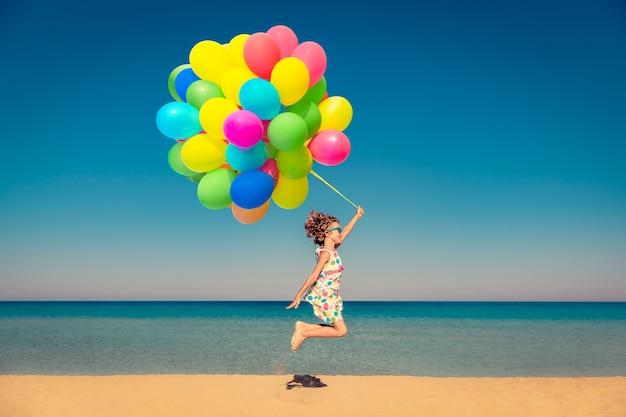 Szczęśliwe dziecko bawiące się jasnymi wielokolorowymi balonami na letnie wakacje dziecko bawiące się na plaży na tle błękitnego morza i nieba