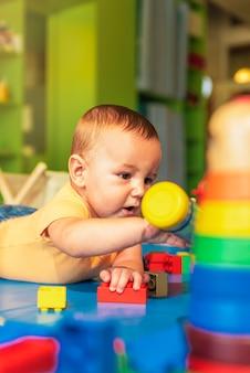 Szczęśliwe dziecko bawiące się klockami w przedszkolu.