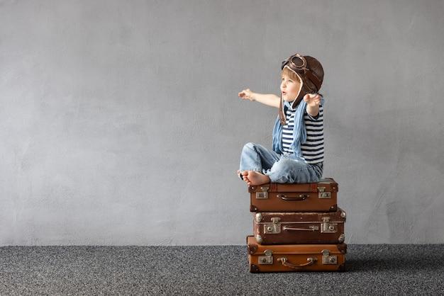 Szczęśliwe dziecko bawiące się na świeżym powietrzu. uśmiechnięty dzieciak marzy o wakacjach i podróżach. koncepcja wyobraźni i wolności