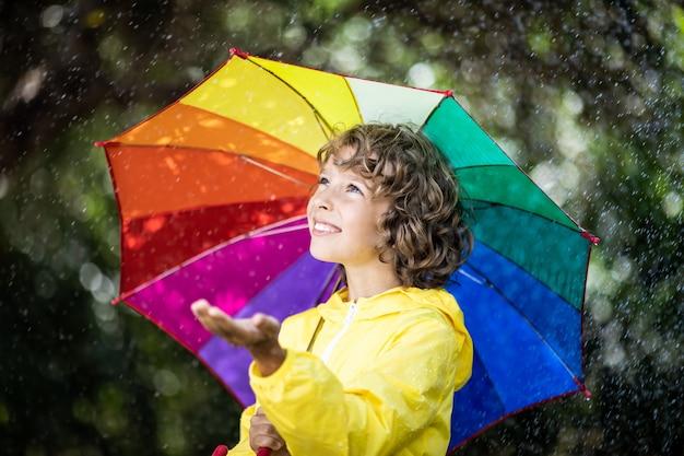 Szczęśliwe dziecko bawiące się w deszczu