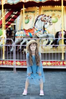 Szczęśliwe dziecko bawiące się w parku rozrywki urocza dziewczynka w pobliżu karuzeli na zewnątrz