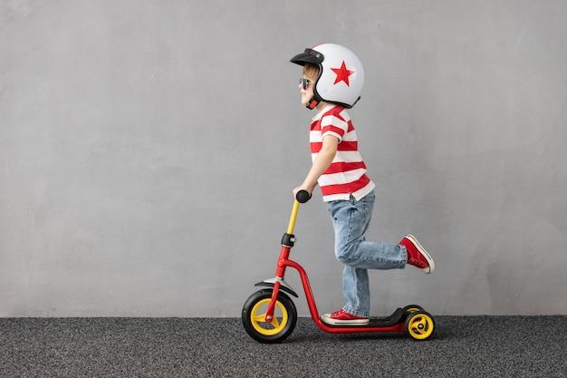 Szczęśliwe dziecko bawić się na świeżym powietrzu. zabawny skuter dla dzieci. zabawa dla dzieci latem