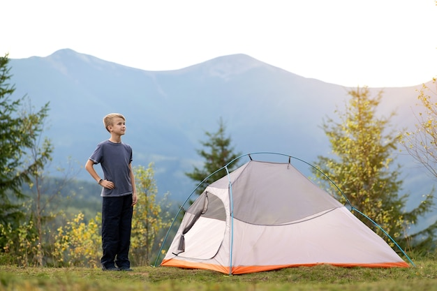 Szczęśliwe dziecko chłopiec stojący w pobliżu namiotu turystycznego na kempingu górskim, ciesząc się widokiem pięknej letniej przyrody