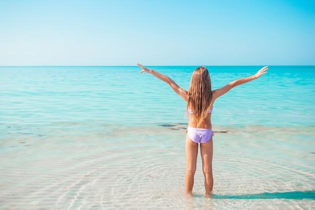 Szczęśliwe dziecko cieszy się tropikalnymi wakacjami na plaży i jest gotowe do kąpieli