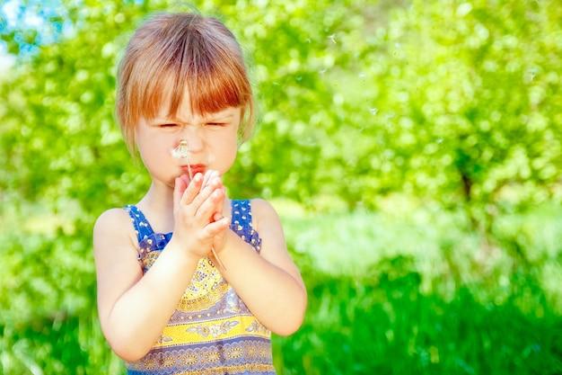 Szczęśliwe dziecko dmuchające mniszka lekarskiego na przyrodę w parku