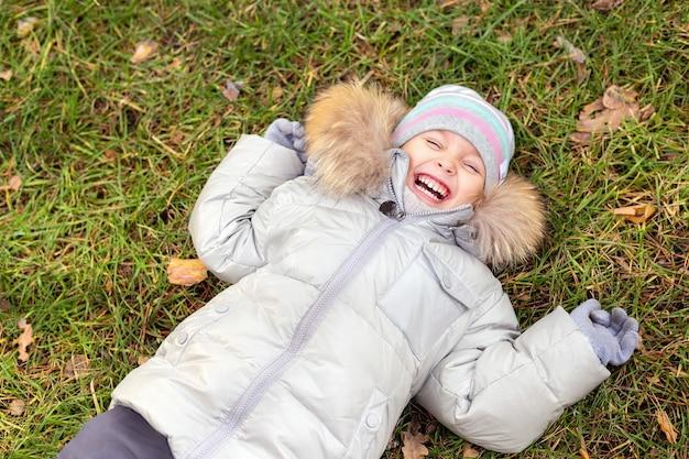 Szczęśliwe dziecko dziewczyna smilling i bawić się jesienią na zewnątrz.