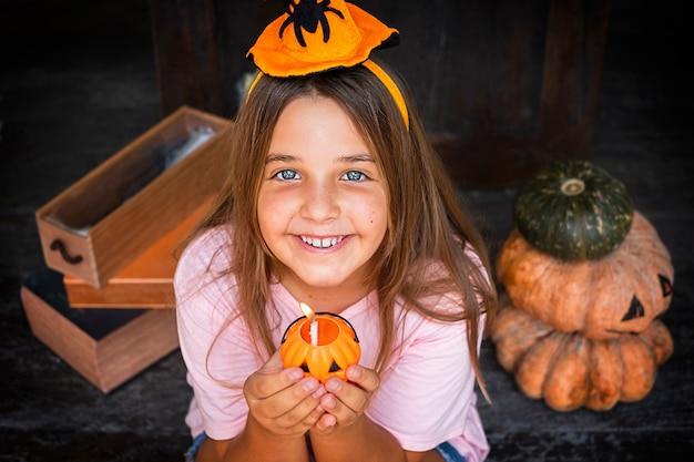 Szczęśliwe dziecko dziewczyna w kapeluszu trzyma dyniową świecę w pobliżu dekoracji halloween