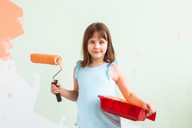 Szczęśliwe dziecko dziewczynka maluje ścianę pomarańczową farbą