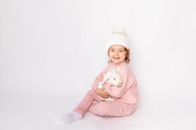 Szczęśliwe dziecko dziewczynka na białym tle na białym tle z króliczkiem w dłoniach w różowym swetrze i kapeluszu uśmiechnięty, miejsca na tekst