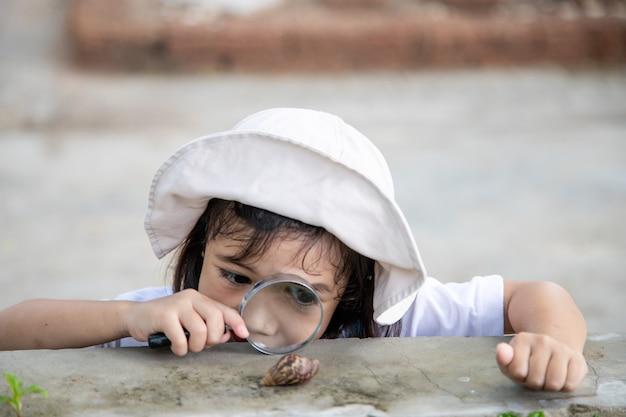 Szczęśliwe dziecko dziewczynka odkrywania przyrody z lupą i ślimakiem. bawi się w ogrodzie. koncepcja dziecka jest gotowa do pójścia do szkoły.