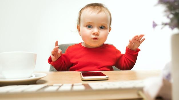 Szczęśliwe dziecko dziewczynka siedzi z klawiaturą nowoczesnego komputera lub laptopa w białym studio
