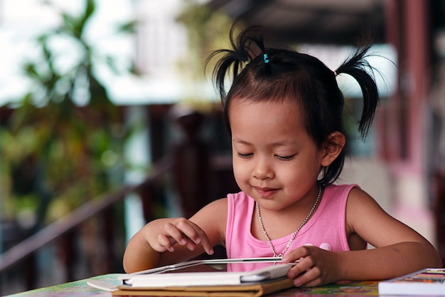 Szczęśliwe dziecko gapi się tablet.