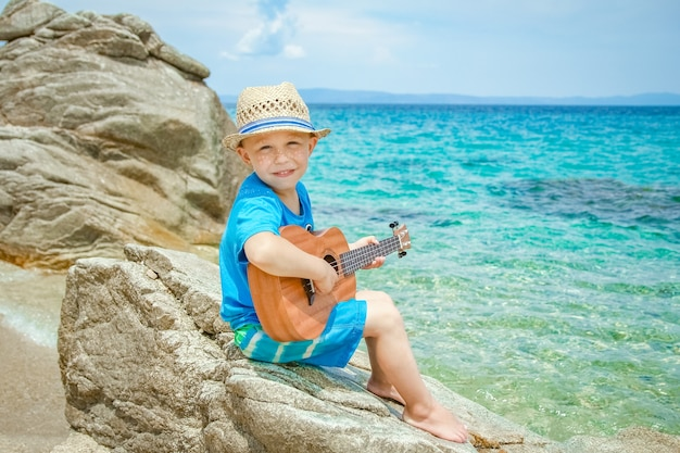 Szczęśliwe dziecko gra na gitarze nad morzem w grecji na tle przyrody
