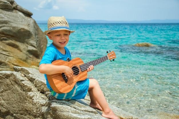 Szczęśliwe dziecko gra na gitarze nad morzem