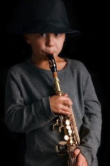 Szczęśliwe dziecko gra na saksofonie w studio