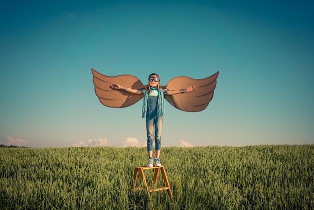Szczęśliwe dziecko grając na zewnątrz w polu latem. koncepcja podróży i wakacji. wyobraźnia i wolność
