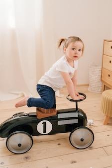 Szczęśliwe Dziecko Grając W Domu. Dziewczyna Z Kucykami Bawi Się W Pokoju I Jeździ Samochodem Z Zabawkami W Stylu Retro. Premium Zdjęcia