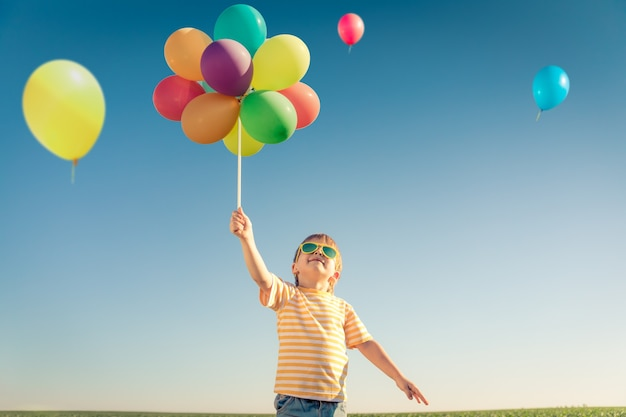 Szczęśliwe dziecko grając z zewnątrz jasne kolorowe balony