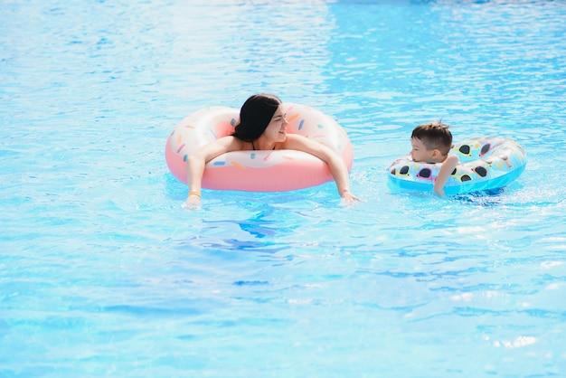 Szczęśliwe dziecko i kobieta bawiące się w basenie z pontonami