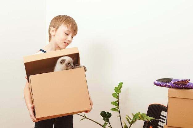 Szczęśliwe dziecko i kot bawią się razem w dniu przeprowadzki w nowym domu. mieszkanie młodej rodziny z dzieckiem i zwierzakiem. słodki dzieciak pomagający rozpakować pudełka