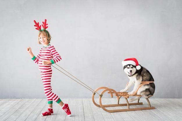 Szczęśliwe dziecko i pies w wigilię dzieciak i zwierzak ubrany w czapkę świętego mikołaja
