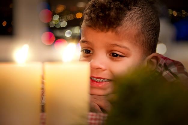 Szczęśliwe dziecko i świece świąteczne. dziecko szczęśliwie patrzy na świece. wakacje są zawsze zabawne. nie mogę się doczekać prezentów.