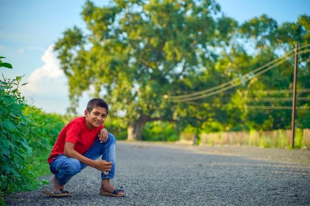 Szczęśliwe dziecko indyjskie bawiące się na ziemi