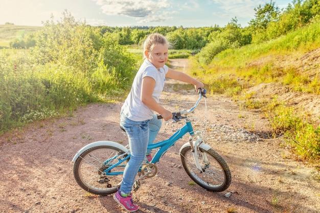 Szczęśliwe dziecko jazda rowerem. młoda dziewczyna na bicyklu w pogodnym lato parku. aktywność letnia zdrowych dzieci w wieku szkolnym. dzieci bawiące się i jeżdżące na rowerze na świeżym powietrzu