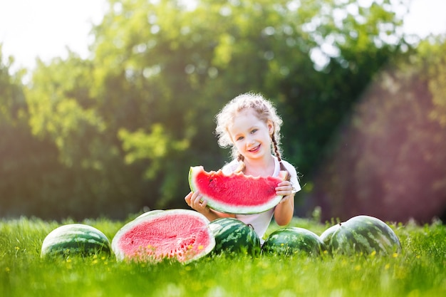 Szczęśliwe dziecko jedzenie arbuza. dziecko je owoce na świeżym powietrzu. mała dziewczynka bawi się w ogrodzie gryzie kawałek arbuza.