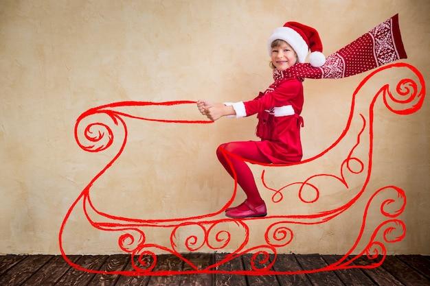 Szczęśliwe dziecko jeździ w wyimaginowanych saniach świętego mikołaja. koncepcja cudu bożego narodzenia