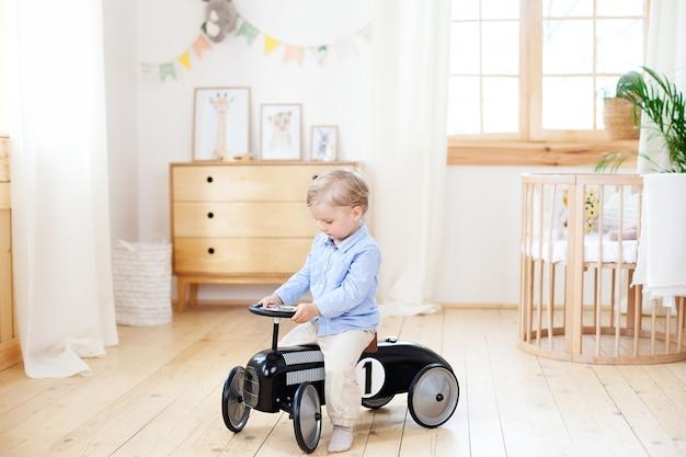 Szczęśliwe dziecko jeździ zabytkowym samochodem w pokoju dziecięcym. zabawne dziecko grające w domu. aktywny mały chłopiec prowadzący samochód dziecięcy w przedszkolu. berbeć jedzie retro samochód, chłopiec w zabawkarskim samochodzie