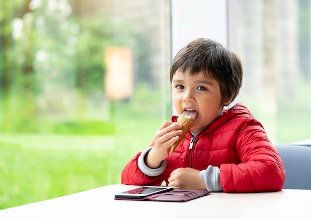 Szczęśliwe dziecko lizanie lodów, relaksujący chłopiec przedszkola siedzi przy stole w kawiarni