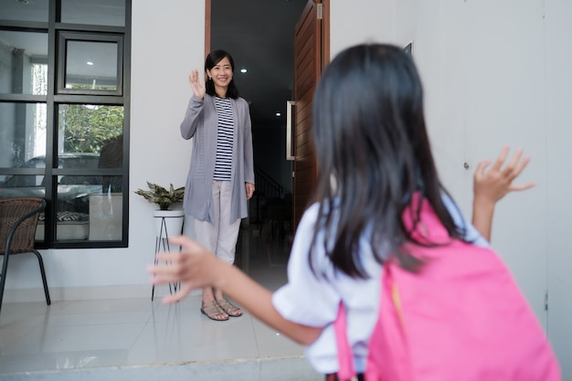 Szczęśliwe dziecko macha na pożegnanie do mamy w domu przed pójściem do szkoły rano