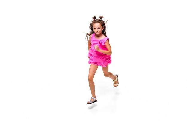 Szczęśliwe dziecko, mała i emocjonalna kaukaska dziewczynka skacząca i biegająca na białym tle