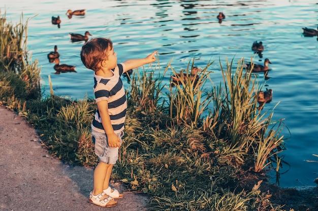 Szczęśliwe dziecko, mały chłopiec patrzy w dół, zamyślony wygląd i trzymając w rękach narośla na zewnątrz.