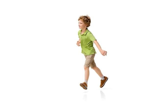 Szczęśliwe dziecko, mały i emocjonalny chłopiec kaukaski skaczący i biegający na białym tle