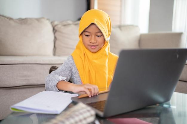 Szczęśliwe dziecko muzułmańskie noszące chustę na głowie uśmiechające się podczas korzystania z laptopa w domu