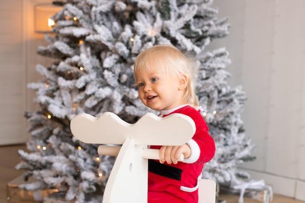 Szczęśliwe dziecko na koniu na biegunach w pobliżu choinki w świątecznie udekorowanym domu