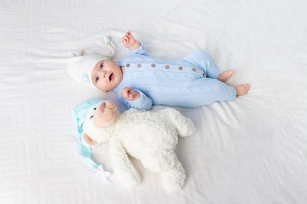 Szczęśliwe dziecko na łóżku w kapturze. tekstylia i pościel dla dzieci. noworodek z misiem zabawka